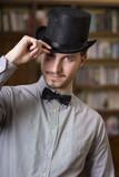 Attractive young man wearing top hat and bow tie