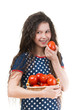 smiling schoolgirl holds basket of tomato