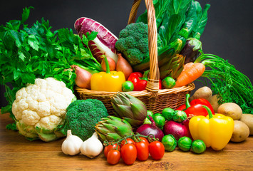 Raw vegetables in wicker basket on wooden table