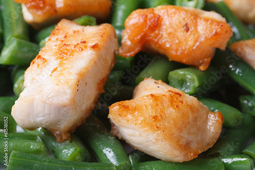 Roast chicken meat on a background of green beans