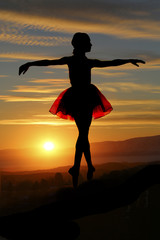 silhouette of young balerina with a sunset background