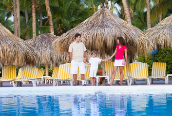 Young family next to a swimming pool at a tropical resort