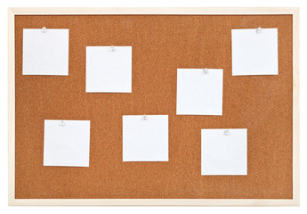 several sheets of paper on bulletin cork board