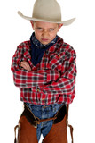 Young cowboy glaring at camera wearing hat and chaps arms folded poster