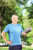 Smiling mature man holding an exercising mat and posing in park