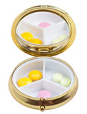 compact pill box with mirror and few tablets