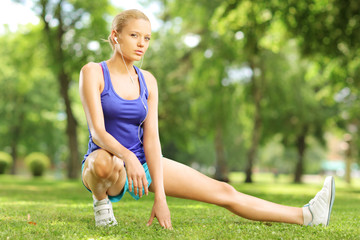 Young blond female exercising in a park