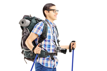 Young male tourist walking with hiking poles