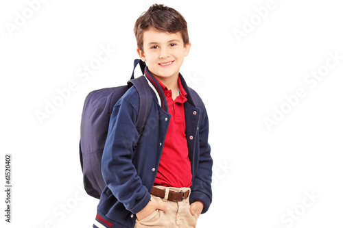 School boy with backpack standing and looking at camera
