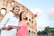 Happy travel couple with tablet by Coliseum, Rome
