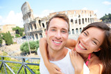 Happy travel couple in piggyback by Coliseum, Rome