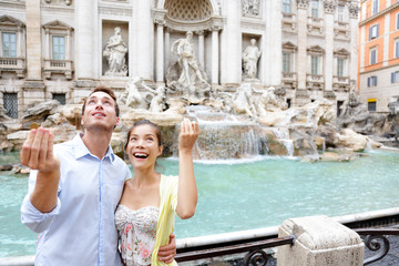 Travel couple trowing coin at Trevi Fountain, Rome
