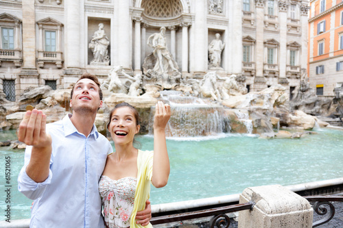 Travel couple trowing coin at Trevi Fountain, Rome - 61521065