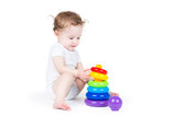 Cute baby playing with a plastic pyramid