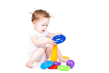 Funny baby playing with a colorful pyramid