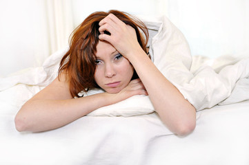red hair woman on bed waking up with hangover and headache