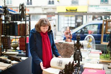 Girl selecting a book on a Parisian flea market