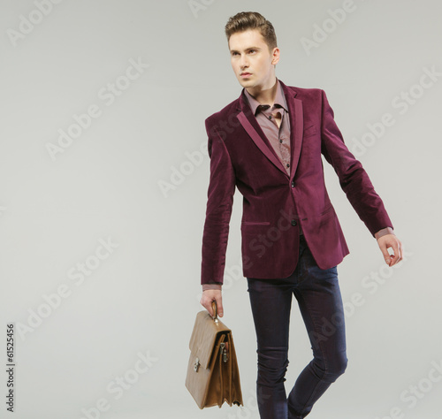 Handsome man carrying the leather handbag