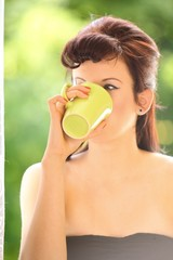 Beautiful Girl Drinking Tea or Coffee. Green Blurred Background