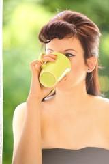 Beautiful Girl Drinking Tea or Coffee. Green Blurred Background