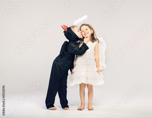 Little devil-boy kissing his angel friend