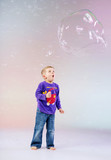 Cute little boy enjoying soap bubbles