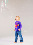 Little cute boy playing a soap bubbles