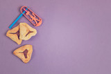 Hamantaschen cookies with grogger on purple background