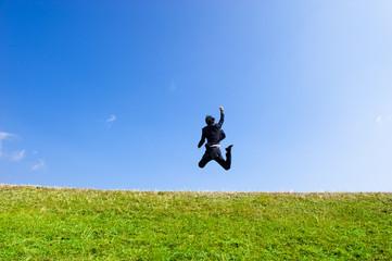 青空に向かって大きくジャンプするスーツの男性