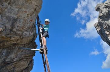 Kind beim Klettern auf Leiter im Klettersteig