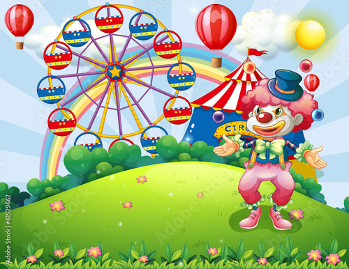 A clown juggling at the hilltop across the carnival