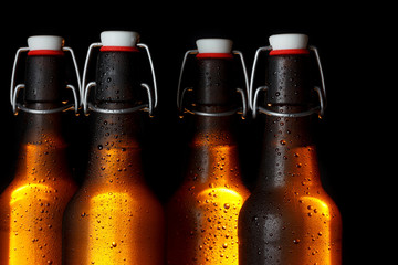 Golden glowing beer bottles on dark background