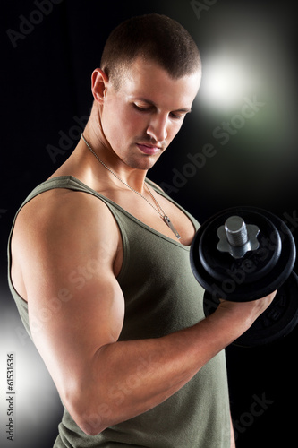 Young muscular man lifts a weight with biceps.