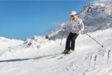 Little skier girl in slope of snow alps