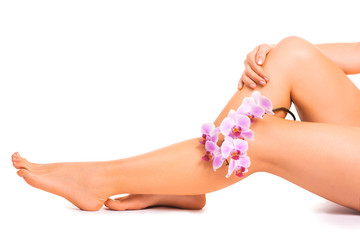 female legs with orchid flower on white