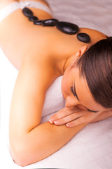 woman in spa salon with hot stones