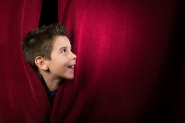 Child appearing beneath the curtain