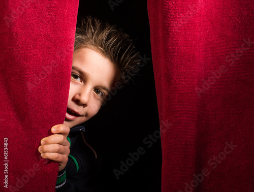 Leinwanddruck Bild Child appearing beneath the curtain