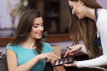 Woman with makeup artist choosing color of eyeshadow