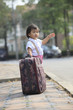 young children standing with big suitcase beside traffic street