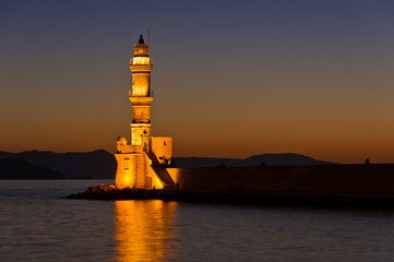 View of Chania harbor with lighthouse at sunset, Crete