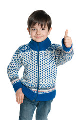 Young boy in a sweater holds his thumb up