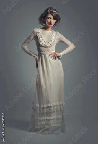 Elegant young woman in white long dress posing indoors