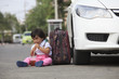 children sitting beside car and drinking beverage