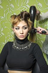 Pretty woman in hair salon drying hair