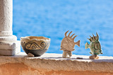 Clay pot and fishes stand on wall