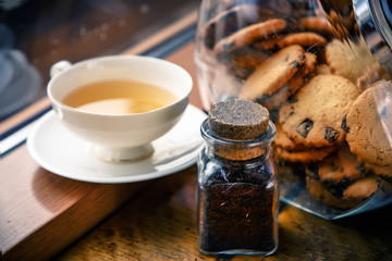 A cup of tea and chocolate chip cookies on the windowsill