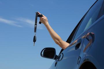 Frau hält Autoschlüssel in die Luft