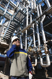refinery worker with main oil and fuel pump