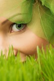 Smiling young woman hiding in a fresh spring grass